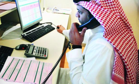 A Saudi investor monitors stock prices on screen.