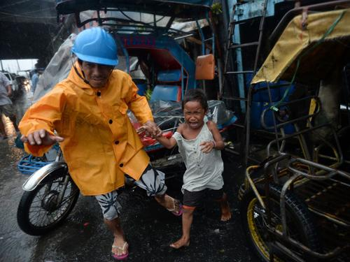 A village official leads a child as he is evacuated from their house at an informal settlers' area as Typhoon Rammasun barrels across Manila on Wednesday.
