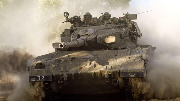 An Israeli Merkava tank rolls along the southern Israeli border with the Gaza Strip following Israeli air strikes in the Palestinian coastal enclave, on July 10, 2014.