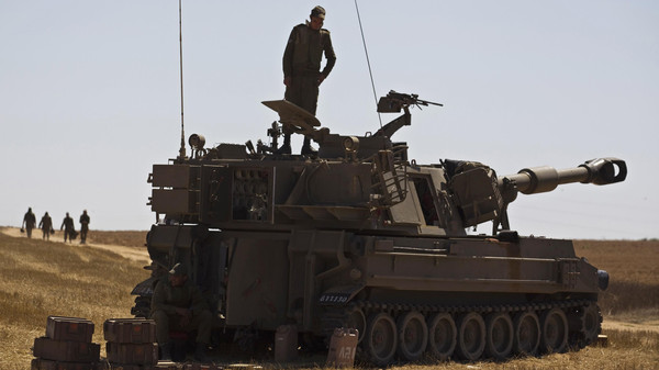 An Israeli soldier stands atop a mobile artillery unit stationed near the border with the Gaza Strip July 9, 2014.