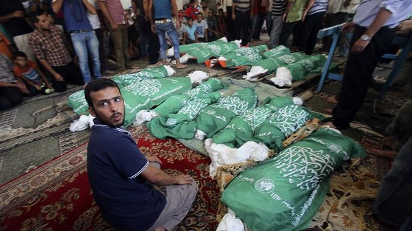 A man sits next to the bodies of Palestinians from Abu Jama'e family, who medics said were killed in an Israeli air strike that destroyed their house, during their funeral at a mosque in Khan Younis in the southern Gaza Strip July 21, 2014.