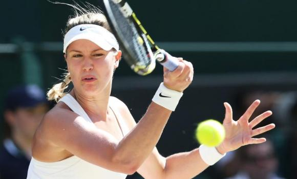 Eugenie Bouchard of Canada returns to Simona Halep of Romania in their semifinal match of the Wimbledon Championships at the All England Lawn Tennis Club, in London.