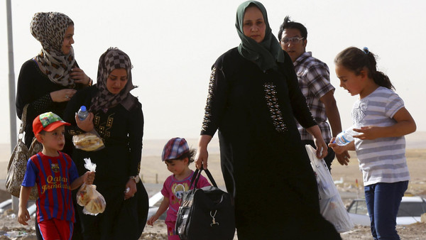 A family fleeing the violence in Mosul waits at a checkpoint on the outskirts of Arbil, in Iraq's Kurdistan region, June 11, 2014.