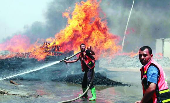 Firefighters try to extinguish a blaze caused by an Israeli tank shelling in the Gaza City's industrial area.