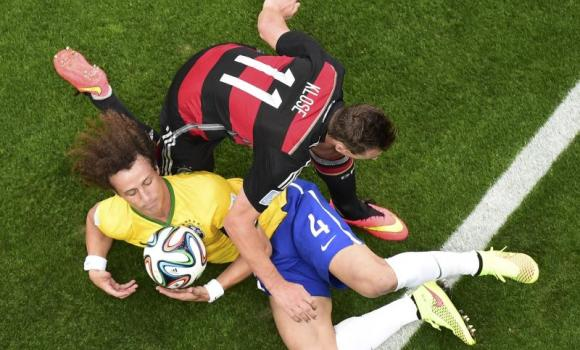 Germany's Miroslav Klose (L) and Brazil's David Luiz fall while fighting for the ball during their 2014 World Cup semi-finals at the Mineirao stadium in Belo Horizonte on Tuesday.