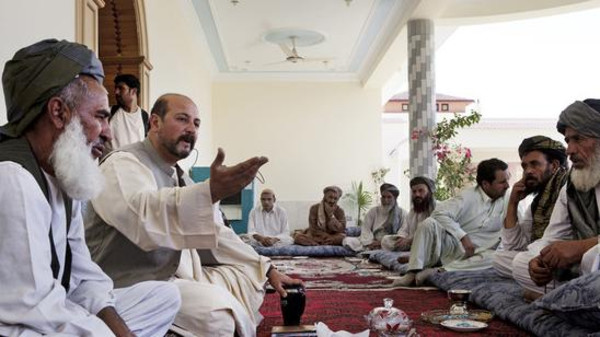 Hashmat Karzai, with hand raised, sits in his mansion surrounded by his hosts, in the village of Karz.