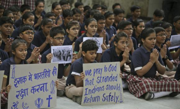 Indian school children hold play cards as they pray for safety of Indians stranded in Iraq, in Ahmedabad, India.
