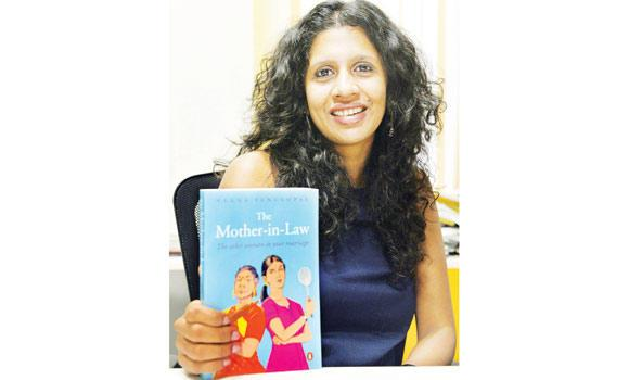 Indian writer Veena Venugopal poses with her book 'The Mother-in-Law' at her home in New Delhi.
