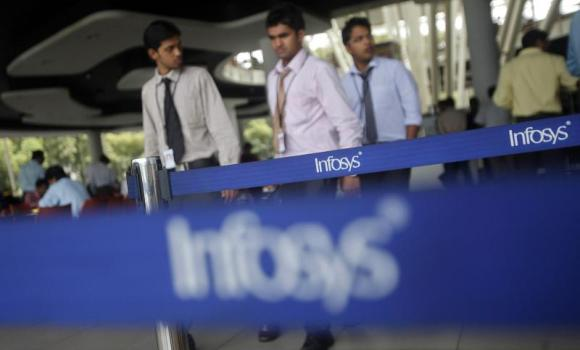 Employees of Infosys walk past company logos at their campus in the Electronic City area in Bangalore.