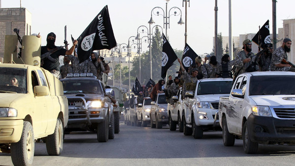 Militant Islamist fighters parade on military vehicles along the streets of Syria's northern Raqqa province June 30, 2014.