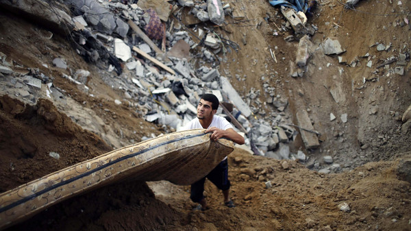 A Palestinian salvages a mattress from the remains of a house, which police said was destroyed in an Israeli air strike, in Khan Younis in the southern Gaza Strip July 21, 2014.