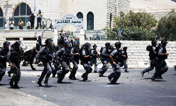 Israeli police move towards Palestinians just after the Friday prayers outside of the Old City in East Jerusalem on Friday, on the first Friday prayer of the holy fasting Muslim month of Ramadan.