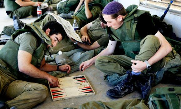 Israeli reserve soldiers play backgammon after coming back from fighting in the Gaza Strip, near the Israel Gaza border on Wednesday.