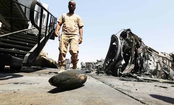 A member of the Libyan security forces inspects the destruction at Tripoli international airport in the Libyan capital on Monday after militiamen stepped up their assault on the country's main airport, which is controlled by rival fighters.