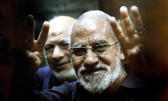 "In this May 8, 2014 photo shows Egyptian Brotherhood's supreme guide Mohamed Badie flashing the ""Rabaa"" sign, which means four in Arabic, remembering those killed in the crackdown on the Rabaa al-Adawiya protest camp in Cairo last year, during his trial at a police academy in Cairo."