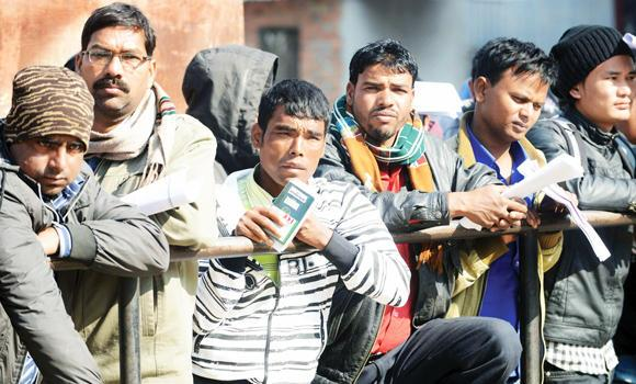 Nepalese migrant workers queue to receive official documents in order to leave Nepal from the Labour Department in Katmandu in this January 27, 2014, file photo. A report commissioned by the Qatar Foundation has recommended that recruitment agencies be banned from charging placement fees on foreign workers, to stop abuses against workers.