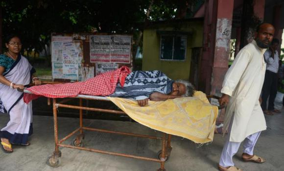 An elderly Indian patient is shifted to a ward while being treated for Japanese encephalitis at the North Bengal Medical College Hospital (NBMCH) on the outskirts of Siliguri on July 24, 2014. Recent outbreaks of encephalitis in India have killed more than 150 people, with health officials on alert fearing the death toll could rise further, state government directors said.
