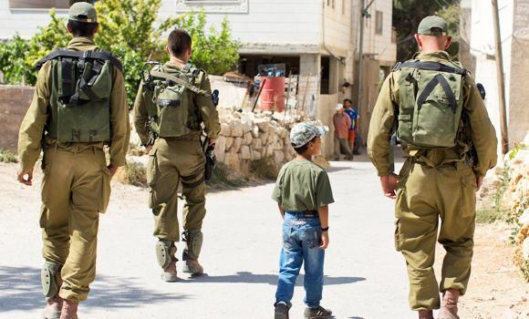 A Palestinian boy walks next to Israeli soldiers.