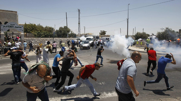 Palestinian protesters run away from tear gas fired by Israeli soldiers during clashes after Friday prayers in the Arab east Jerusalem neighbourhood of Ras al-Amud.