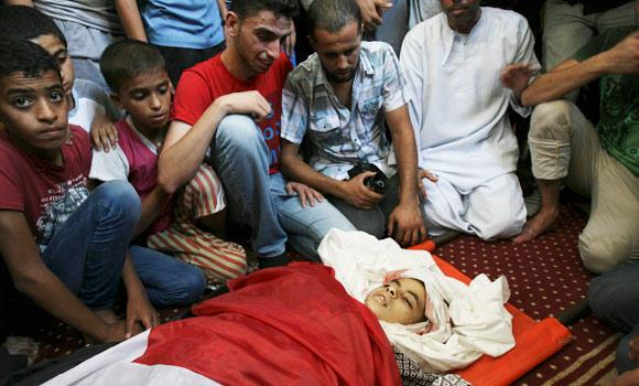 Palestinian relatives mourn over the body of Noor Alnajedy, 10, who was killed during an Israeli air strike on a building near his family house, at the main mosque during his funeral in Rafah refugee camp, southern Gaza Strip, on Friday.