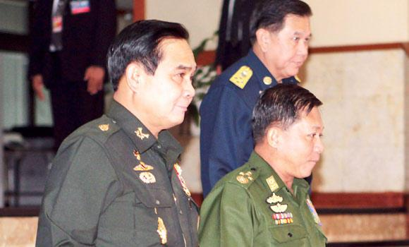 Thai Army chief General Prayuth Chan-ocha (L) walks with Myanmar's Commander-in-Chief General Min Aung Hlaing (C) and Thai Supreme Commander General Thanasak Patimaprakorn after a meeting at the Royal Thai Army headquarters in Bangkok, in this July 4, 2014 photo.