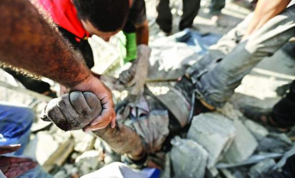 Rescue workers remove the body of a Palestinian from under the rubble of his home following an Israeli airstrike on Beit Hanun, Gaza Strip.