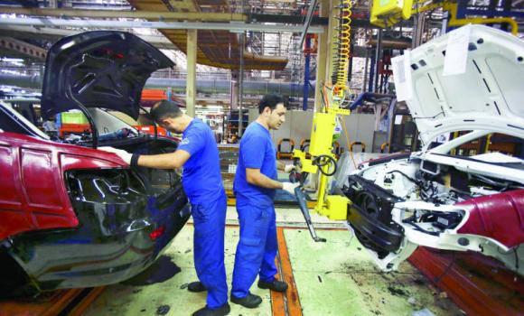 Workers assemble a car at an automobile manufacturing plant near Tehran.