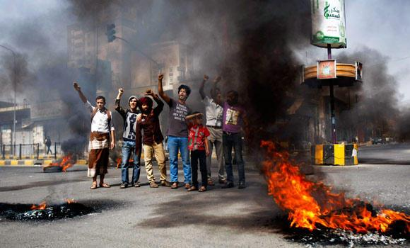 Yemenis chant slogans after setting tires on fire during a protest against the inflation of fuel prices in Sanaa, Yemen, on Wednesday.