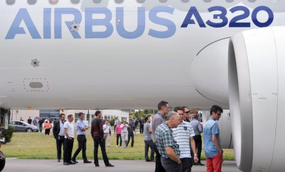 European plane manufacturer Airbus staff members look at an engine of the first copy for test of the 200 medium-haul Airbus A320neo passenger plane which leaves its hangar at the Airbus plant in Saint-Martin-du-Touch, near Toulouse, southern France.