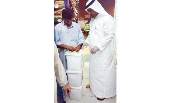 A Commerce Ministry official seals contaminated food packets seized from a warehouse in Makkah.