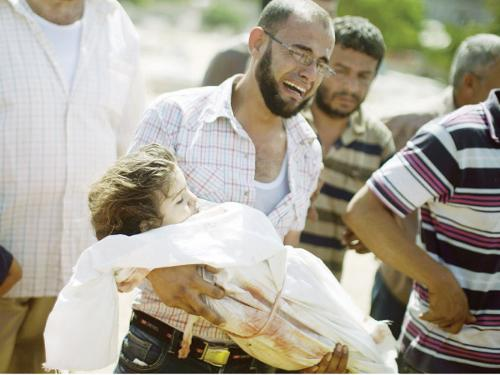 A Palestinian relative carries the body of a child during the funeral of eight members of Abu Jarad family who were killed overnight in an Israeli strike on on Saturday in Beit Lahia, north of the Gaza strip.
