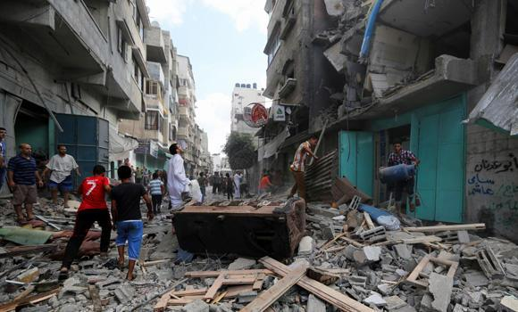 Palestinians inspect the rubble of a building to pick up their usable belongings after it was hit by an Israeli missile strike in Gaza City on Friday.