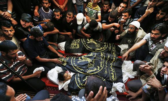 Mourners gather at a funeral at a mosque in Rafah, southern Gaza Strip, on Tuesday, for Sarah Omar el-Eid, 4, bottom, and her father, Omar, 26, center, and her uncle Jihad, 27, top. The three were killed by an Israeli strike late Monday.