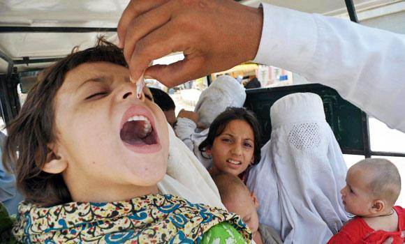 A Pakistani health worker administers polio vaccination drops to a girl in a van in Bannu, in this June 26, 2014 photo.