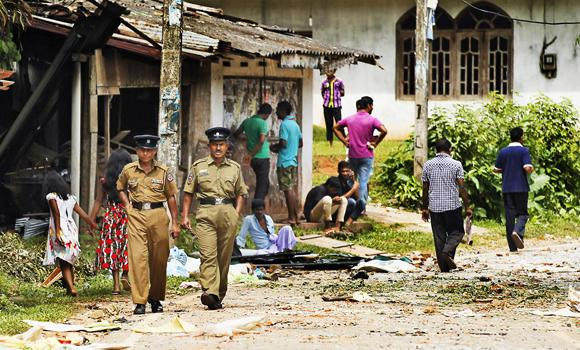 Police officers walk through a Muslim neighborhood in Darga Town, in Aluthgama about 50 km south of Colombo.