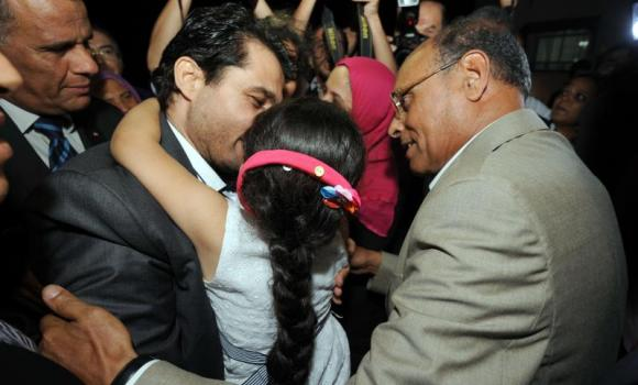 Embassy employee Mohamed Ben Cheikh (2nd-L) is greeted by daughter (C) and Tunisian President Moncef Marzouki (R) on the tarmac on June 30, 2014 in Tunis.