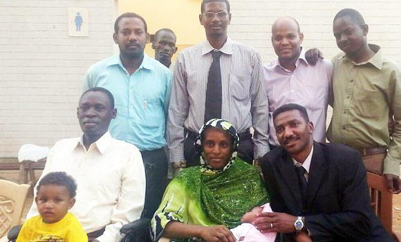 In this file handout picture obtained from the legal team and taken with a smart phone, Meriam Yahia Ibrahim Ishag (seated C), a Christian Sudanese woman sentenced to hang for apostasy last month, poses for a picture with her husband Daniel Wani, a US citizen originally from South Sudan (L), her newborn baby and the couple's 20-month-old son, one of her lawyers Mohanad Mustafa (R), and other members of the legal team at an undisclosed location in Khartoum, in this June 23, 2014 photo.