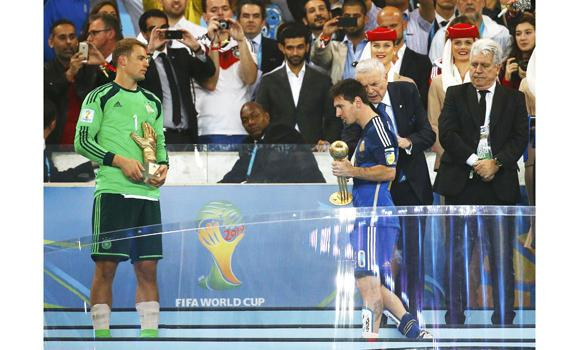 Argentina's Lionel Messi (3rd R) holds the Golden Ball trophy as Germany's goalkeeper Manuel Neuer (L) holds the Golden Glove trophy after their 2014 World Cup final at the Maracana stadium in Rio de Janeiro on Sunday.