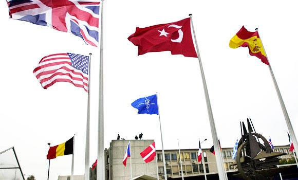 In this April 2, 2004, file photo, flags blow in the wind in front of NATO headquarters in Brussels.