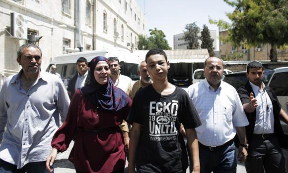 "Tariq Abu Khder (C), a Palestinian-US teenager who was allegedly beaten during police custody, is escorted by his father (L), mother (2nd-L) and Ahmed Tibi (2nd-R), Israeli Arab member of the Knesset (Israeli parliament), out of Jerusalem Magistrates Court following a hearing on July 6, 2014. Tariq Abu Khder, who was arrested in Shuafat during violent clashes between stonethrowers and Israeli riot police, ""was given nine days house arrest in Beit Hanina for the duration of the investigation"" into stonethrowing allegations."