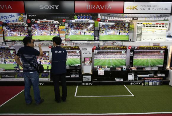 A shopper (L) looks at Sony Corp's Bravia television sets screening a soccer match at an electronics retail store in Tokyo.