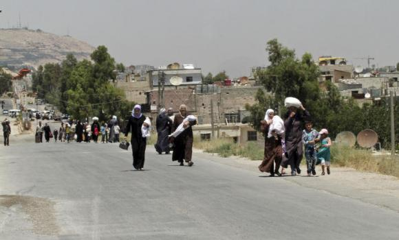 Syrians carry foodstuff as they return to the rebel-held Damascus suburb of Moadamiyeh, following the entry of some 13 Syrian Red Crescent trucks loaded with 1,000 food parcels under the supervision of the UN, the Red Crescent and in coordination with the Syrian government, near Damascus, Syria, on Monday.
