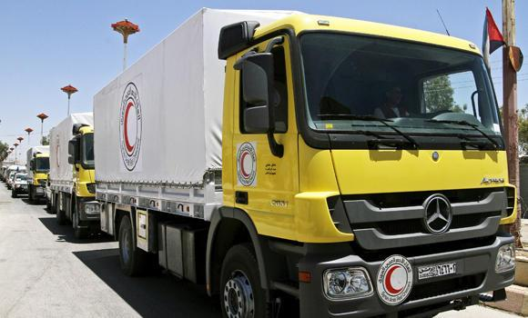 Some 13 Syrian Red Crescent trucks loaded with 1,000 food parcels under the supervision of the UN, the Red Crescent and in coordination with the Syrian government, prepare to distribute aid to tens of thousands of besieged Syrians inside the rebel-held Damascus suburb of Moadamiyeh, Syria, on Monday. A year's blockade on Moadamiyeh resulted in widespread hunger-related illness and death among its residents.