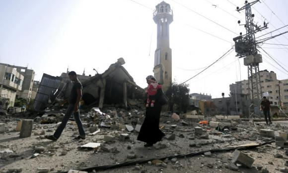 Palestinians walk past the ruins of the Al-Tawfeeq mosque after it was hit by an Israeli missile strike in the Nuseirat refugee camp, central Gaza Strip.