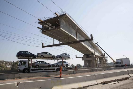 Trucks drive past a railway bridge under construction, planned to connect the northern Israeli city of Haifa to Beit Shean.