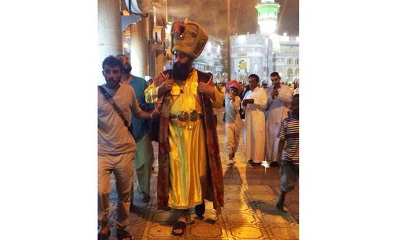 The man in a medieval dress draws everyone's attention in the Grand Mosque.
