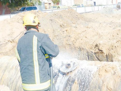 A firefighter extinguishes the fire that broke out when workers tried to remove a fuel tank.