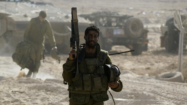 An Israeli soldier carries a weapon near the border with the Gaza Strip July 27, 2014.