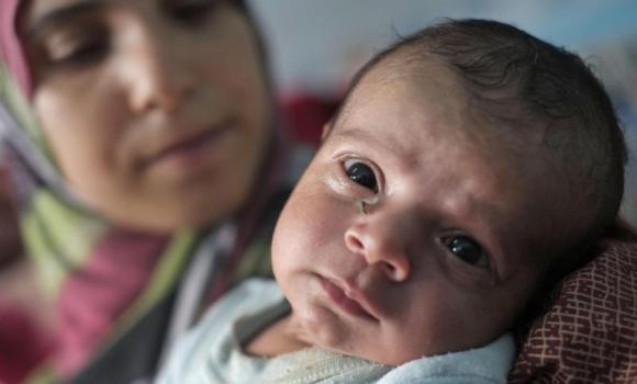 Displaced Palestinian Emada Al Attar, 23, holds her 16-day-old baby boy Anous in a classroom where they sleep at a UN school. The family had sought refuge there from the war, in Gaza City, Gaza Strip.