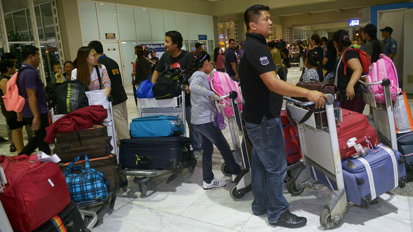 Filipino workers evacuated out of strife-torn Libya stand after their arrival at Ninoy Aquino International Airport in Manila on August 16, 2014.